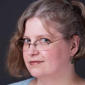 Studio headshot of Stephanie Zvan looking over her glasses.